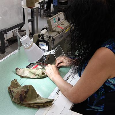 Woman makes personal protective equipment for the military as a part of an AbilityOne contract.